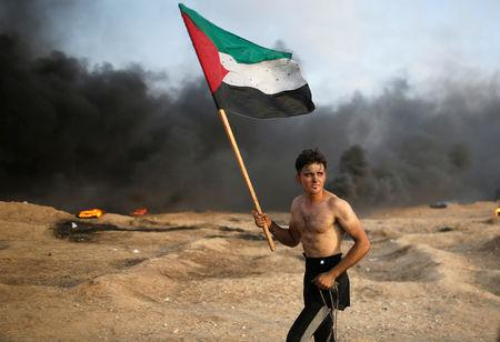 A demonstrator holds a Palestinian flag during a protest calling for lifting the Israeli blockade on Gaza and demanding the right to return to their homeland, at the Israel-Gaza border fence in Gaza October 19, 2018. REUTERS/Mohammed Salem