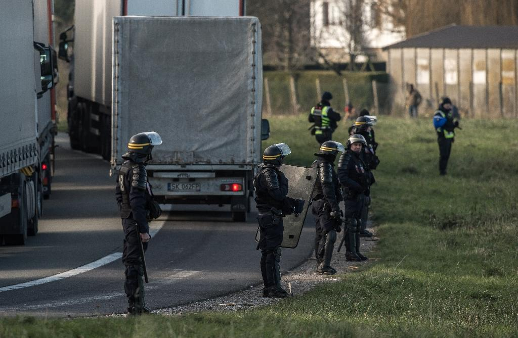 French riot police guard the road after migrants seeking to cross to Britain tried to mount trucks near the Eurotunnel in Coquelles, near Calais, in January 2016