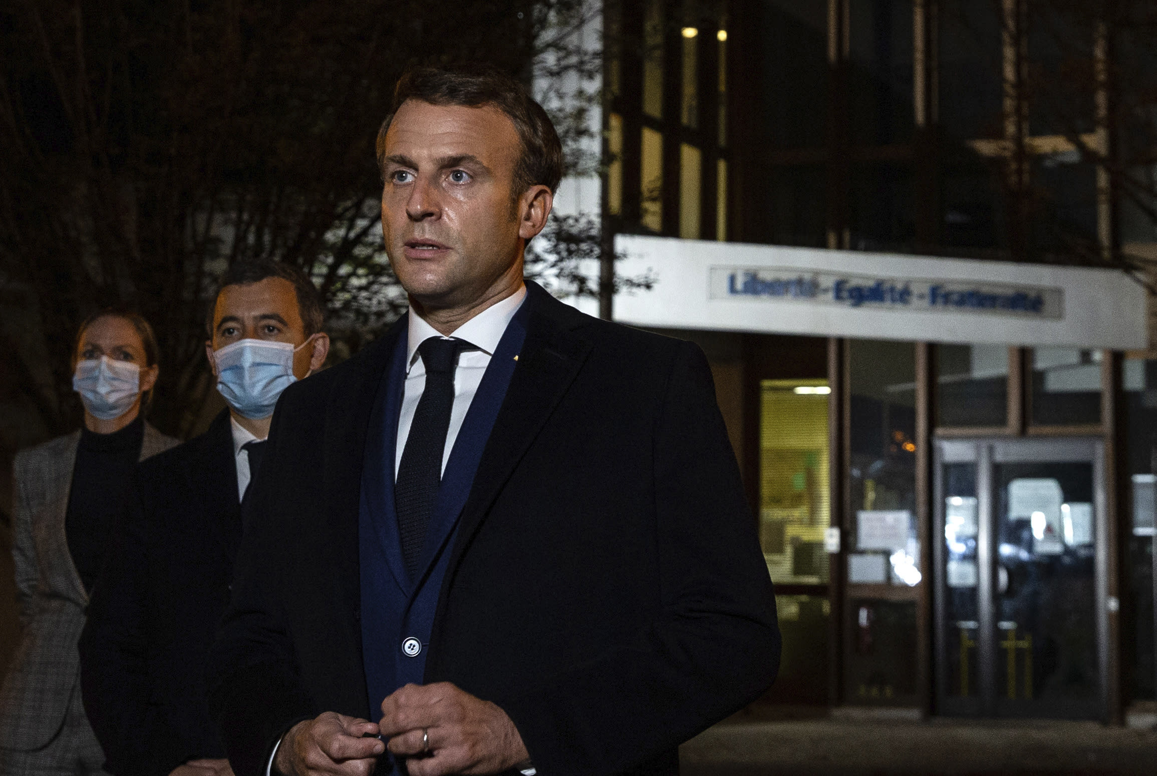 """French President Emmanuel Macron, flanked by French Interior Minister Gerald Darmanin, second left, speaks in front of a high school Friday Oct.16, 2020 in Conflans Sainte-Honorine, northwest of Paris, after a history teacher who opened a discussion with high school students on caricatures of Islam's Prophet Muhammad was beheaded. French President Emmanuel Macron denounced what he called an """"Islamist terrorist attack"""" against a history teacher decapitated in a Paris suburb Friday, urging the nation to stand united against extremism. (Abdulmonam Eassa, Pool via AP)"""