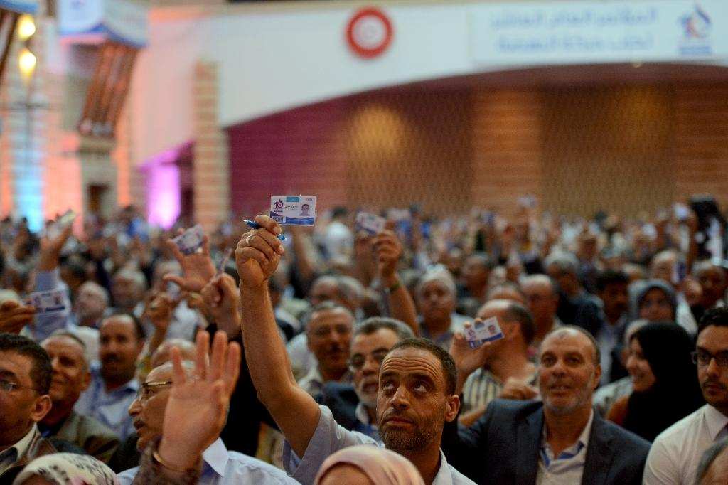 Tunisian Islamist Ennahdha Party members raise their party ID to vote during the discussions on May 22, 2016, in Hammamet on the third-day of the Ennahdha congress