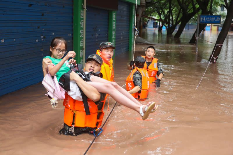Paramilitary police officer evacuates a resident while he is wading through floodwaters following a heavy rainfall in Wanzhou of Chongqing