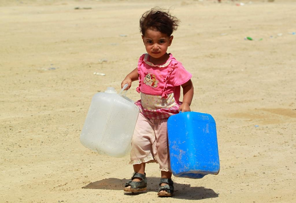 A displaced Iraqi child who fled Anbar province due to the ongoing conflict between pro-government forces and Islamic State (IS) group jihadists, carries jerrycans at a makeshift camp for internally displaced persons (AFP Photo/Haidar Hamdani)