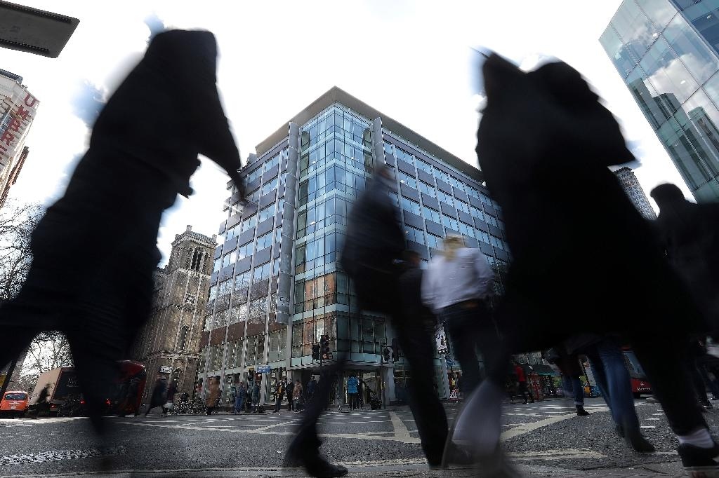 Pedestrians pass the shared building which houses the offices of Cambridge Analytica in central London on March 21, 2018 (AFP Photo/Daniel LEAL-OLIVAS)