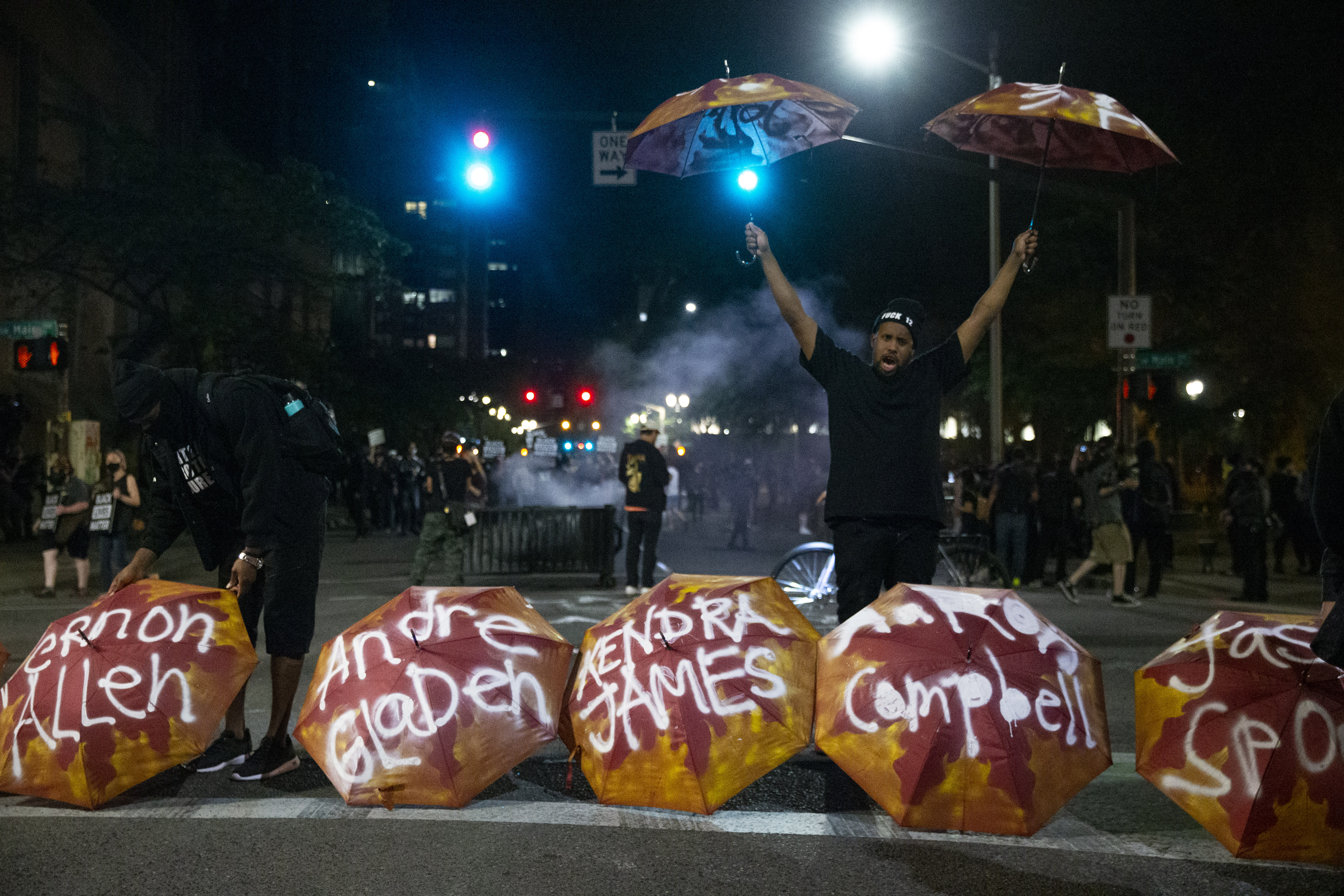 Umbrellas bearing the names of people killed by police were displayed at SW 3rd and Main as Portland protesters gather downtown on Friday, July 10, 2020. (Dave Killen/The Oregonian via AP)