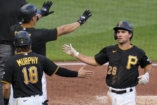 Pittsburgh Pirates' Adam Frazier (26) is welcomed by John Ryan Murphy (18) and Jose Osuna, left rear, after they scored on a single by Pittsburgh Pirates' Ke'Bryan Hayes off St. Louis Cardinals starting pitcher Carlos Martinez, and an error by right fielder Tommy Edman, during the fourth inning of the first baseball game of a doubleheader in Pittsburgh, Friday, Sept. 18, 2020. (AP Photo/Gene J. Puskar)