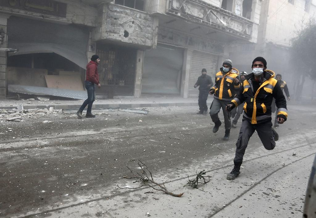 Syrian rescuers and civilians running from the site of a Syrian government bombardment in Hamouria last week, in the Eastern Ghouta region just outside Damascus (AFP Photo/ABDULMONAM EASSA)