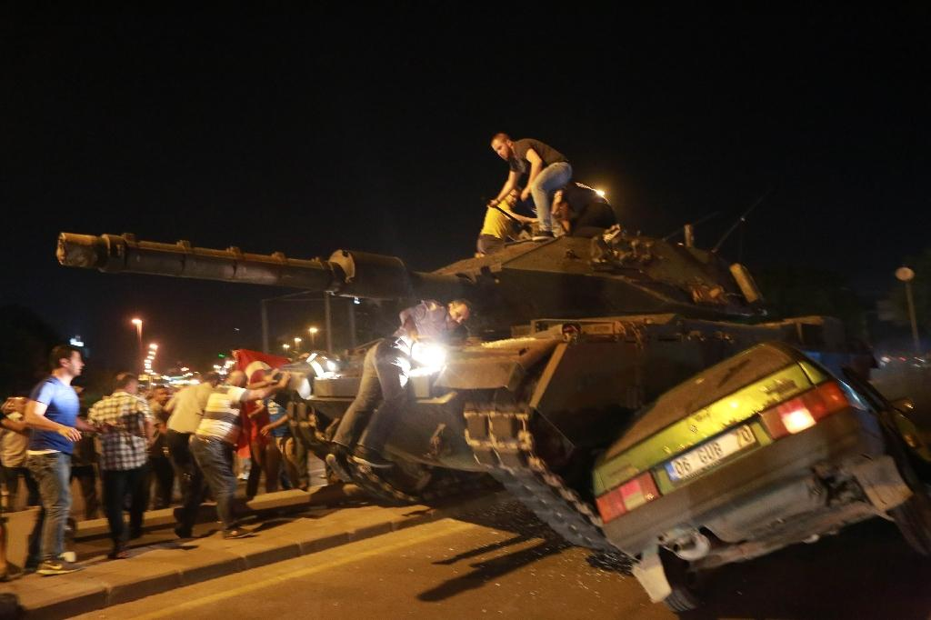 Turkish pro-regime supporters climb onto a tank as it runs over a car during a protest against the military in Ankara on July 16, 2016 (AFP Photo/Adem ALTAN)