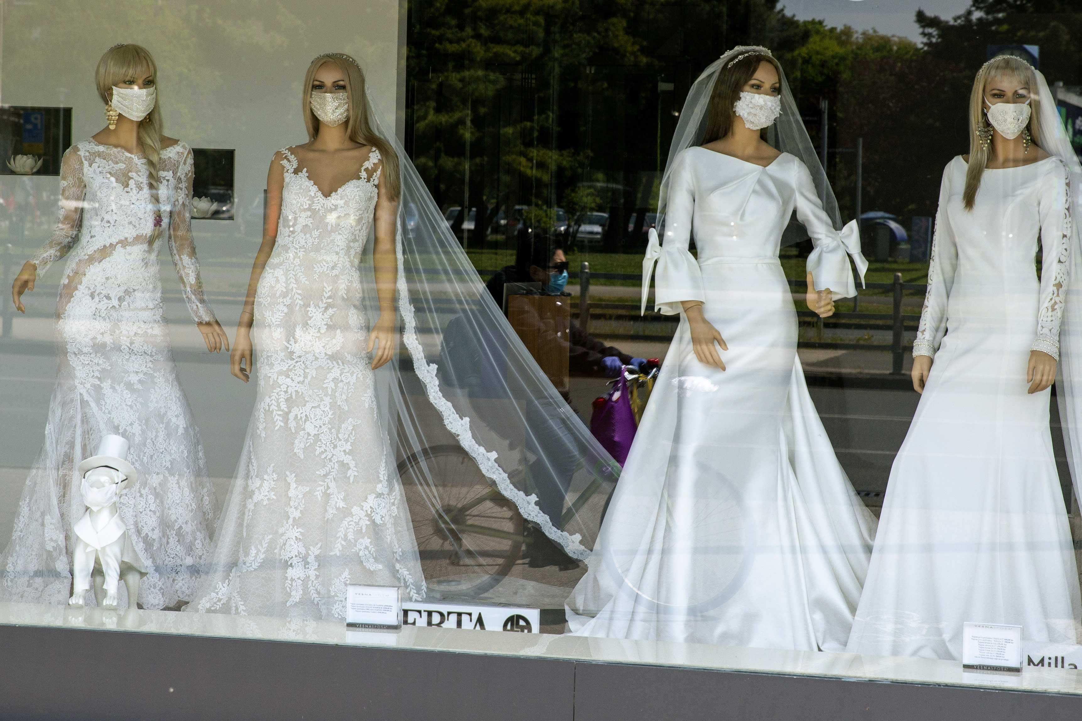 FILE - A masked cyclist is reflected in the window of a wedding dress store with mannequins wearing face masks, in Zagreb, Croatia on April 23, 2020. Now that weddings have slowly cranked up under a patchwork of ever-shifting restrictions, horror stories from vendors are rolling in. Many are desperate to work after the coronavirus put an abrupt end to their incomes and feel compelled to put on their masks, grab their cameras and hope for the best. (AP Photo/Darko Bandic, File)