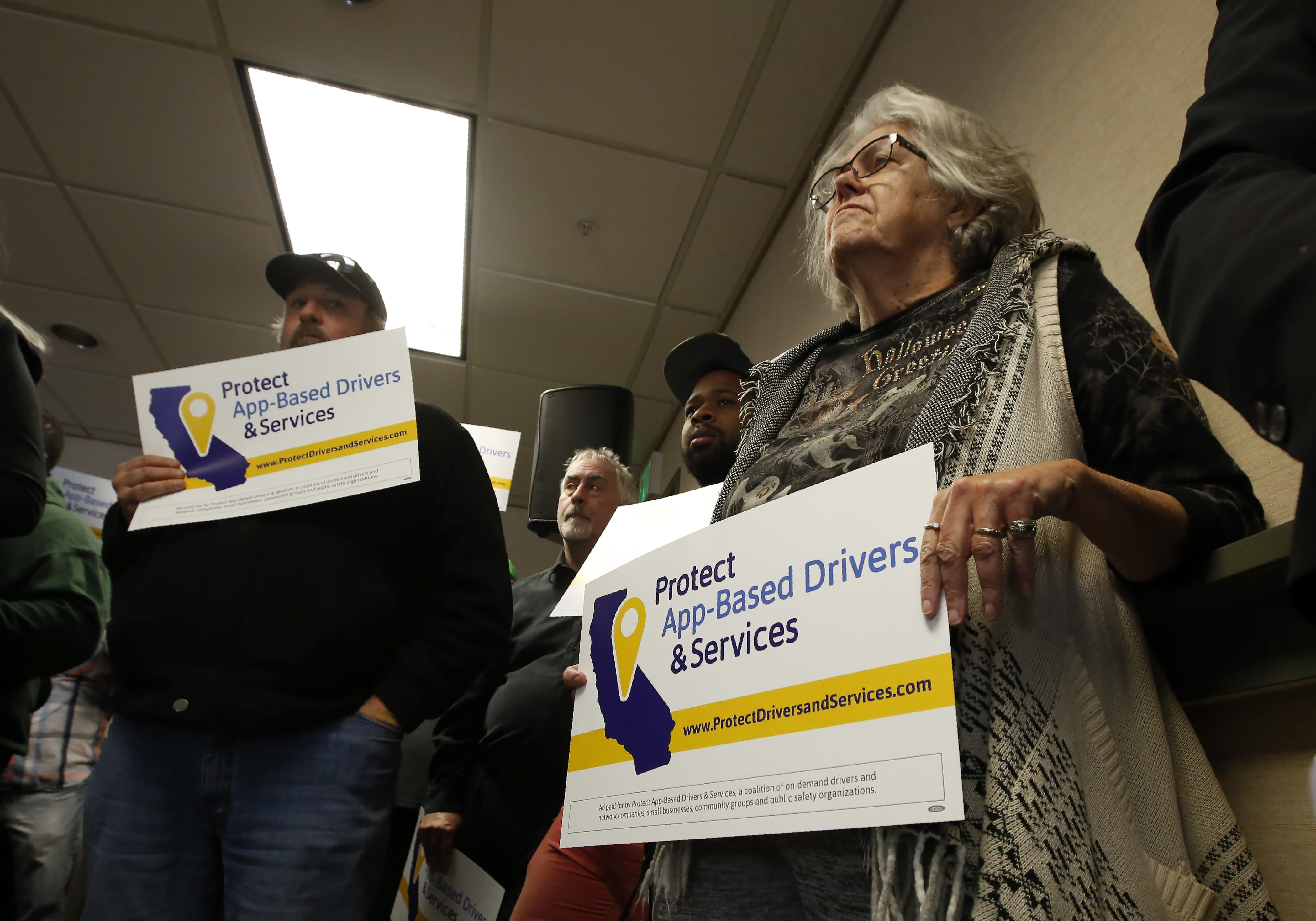 Carla Shrive, right, who drives for various gig into companies, joined other drivers to support a proposed ballot initiative challenging a recently signed law that makes it harder for companies to label workers as independent contractors, in Sacramento, Calif., Tuesday, Oct. 29, 2019. A group called Protect App-Based Drivers and Services announced Tuesday that it will push a ballot initiative guaranteeing that drivers remain independent contractors but also receive a minimum wage and money for health insurance. (AP Photo/Rich Pedroncelli)