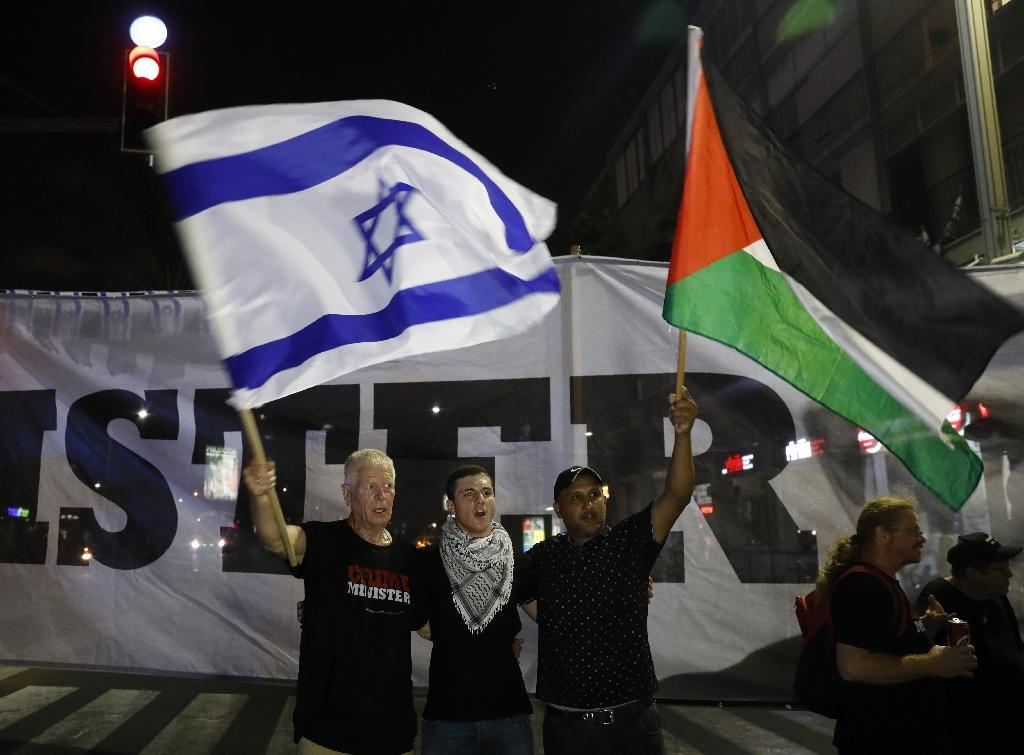 Arab Israelis and their supporters carry a Palestinian flag (R) and an Israeli flag during a protest against the Jewish Nation-State Law in the Israeli coastal city of Tel Aviv on August 11, 2018 (AFP Photo/Ahmad GHARABLI)