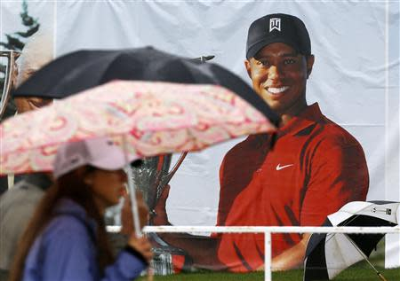 Golf fans walk past a poster of Tiger Woods during a rain delay at the BMW Championship golf tournament at the Conway Farms Golf Club in Lake Forest, Illinois