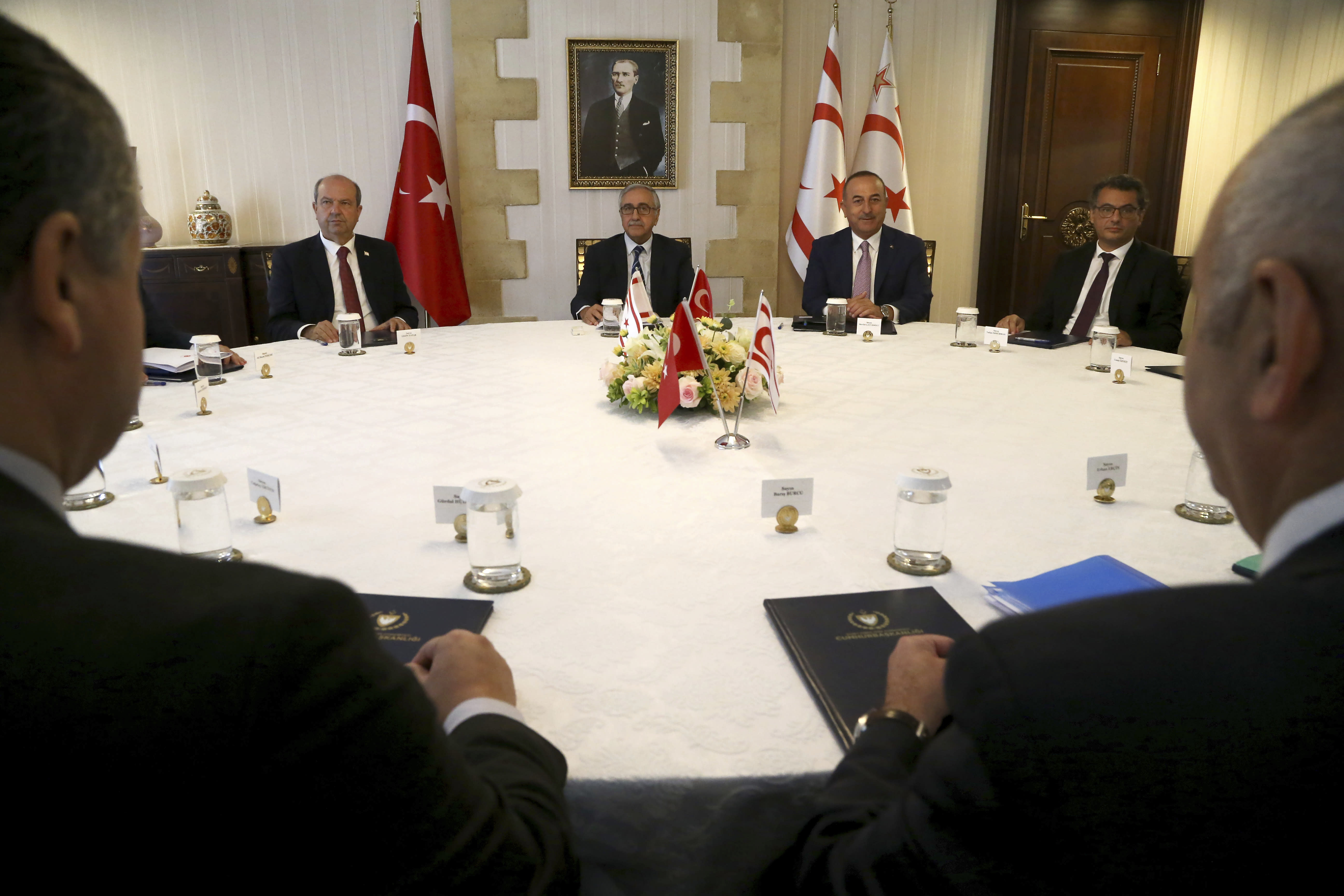Turkish Foreign Minister Mevlut Cavusoglu, center right, and Turkish Cypriot leader Mustafa Akinci, center left, during a meeting in the Turkish occupied area in the northern part of divided capital Nicosia, Cyprus, Monday, Sept. 9, 2019. Cavusoglu is in the northern part of divided Cyprus for three-day visit. (AP Photo/Petros Karadjias)