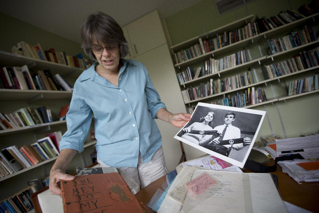 """In this photo taken Tuesday, Aug. 27, 2013, Mary Beth Tinker, 61, holds up an old photograph of herself with her brother during an interview with the Associated Press in Washington. Tinker was just 13 when she spoke out against the Vietnam War by wearing a black armband to her Iowa school in 1965. When the school suspended her, she took her free speech case all the way to the U.S. Supreme Court and won. Her message: Students should take action on issues important to them. """"It's better for our whole society when kids have a voice,"""" she says. (AP Photo/Manuel Balce Ceneta)"""