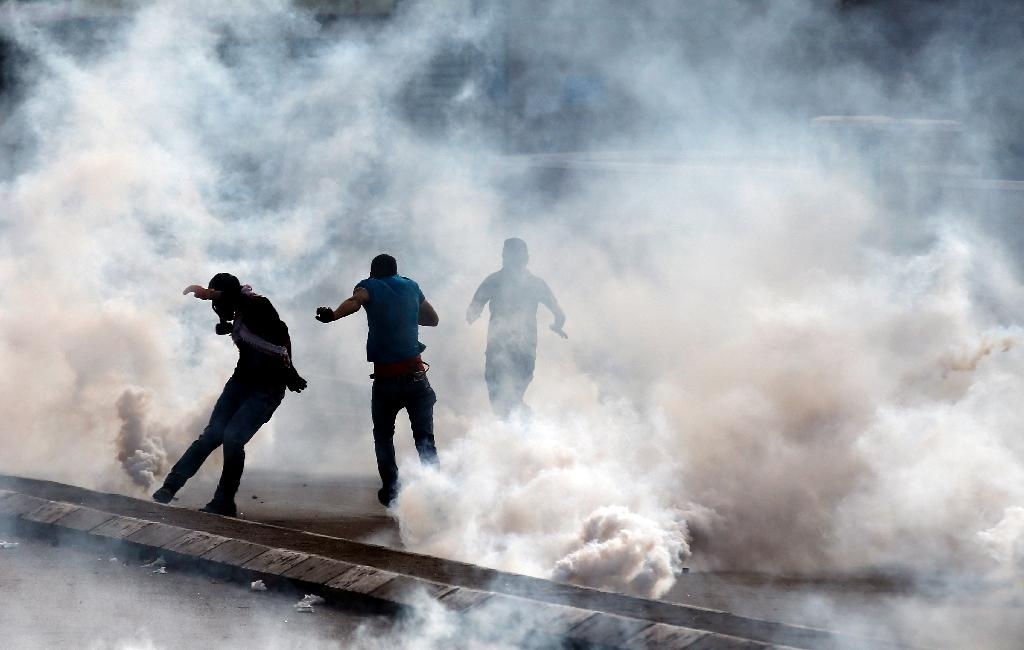 Palestinian demonstrators run for cover after Israeli security forces fired tear gas during clashes in the West Bank city of Bethlehem, on October 13, 2015