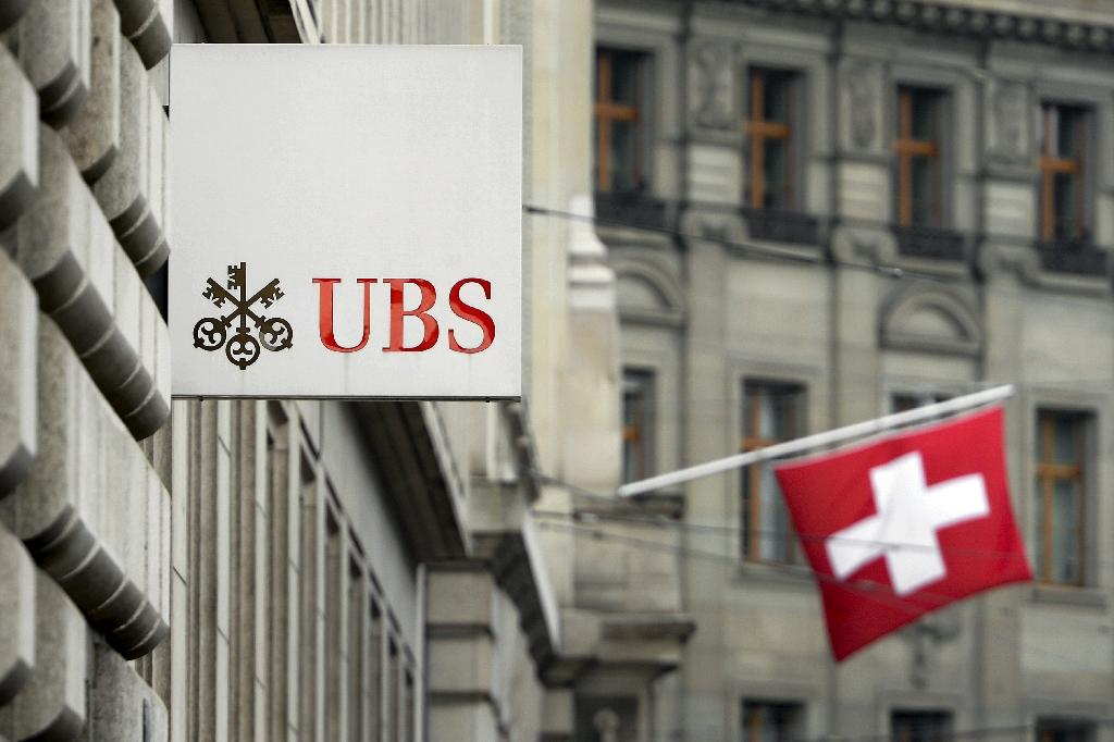 A Swiss flag is seen behind a sign of Swiss bank giant UBS on June 11, 2013 in Basel. AFP PHOTO / FABRICE COFFRINI (AFP Photo/Fabrice Coffrini)