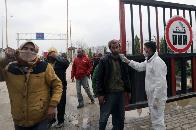Health worker tests a man as part of security measures to avoid coronavirus, at the Bab el-Salam border crossing between the Syrian town of Azaz and the Turkish town of Kilis