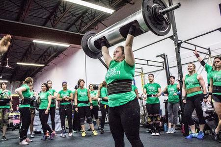 """A participant in the May Queen Spring Strongwoman competition lifts an automotive """"log press"""" in Lancaster, Pennsylvania April 25, 2015. Courtesy of Amanda Kulik/Handout via REUTERS"""