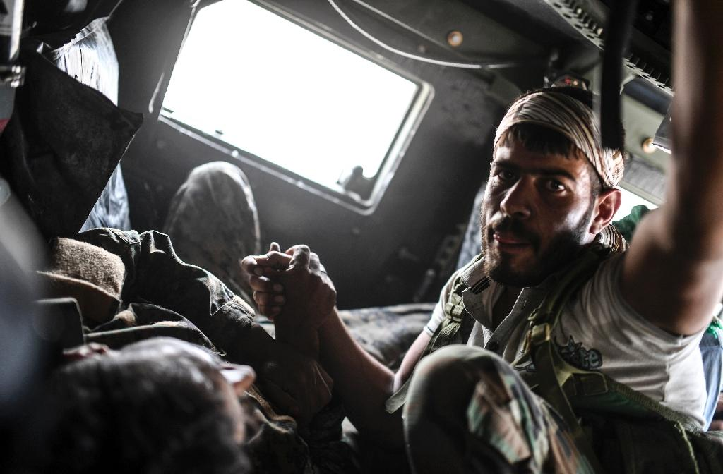 A member of the Syrian Democratic Forces comforts his wounded comrade Ibrahim who was shot by a jihadist sniper as they drive towards a medical centre on the eastern frontline of Raqa (AFP Photo/BULENT KILIC)