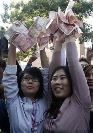 Anti-government protesters hold Thai banknotes to donate to their leader Suthep Thaugsuban during a rally at a major business district in Bangkok December 20, 2013. REUTERS/Kerek Wongsa