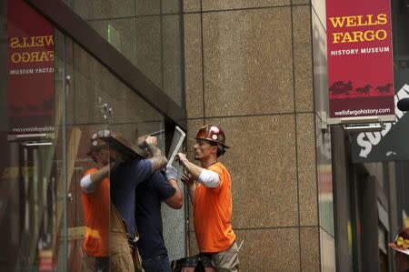 Workers remove shattered glass from the entrance to the Wells Fargo History Museum in San Francisco, California January 27, 2015. REUTERS/Robert Galbraith