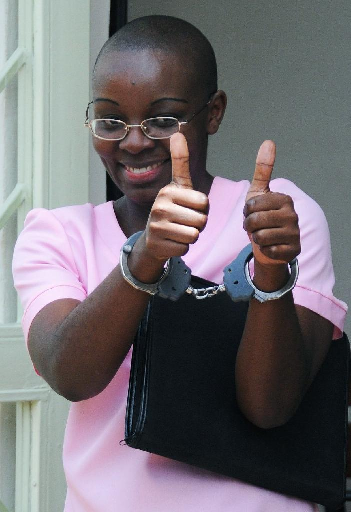 Rwandan opposition leader Victoire Ingabire gives a thumbs-up sign as she leaves the courtroom at her trial in Kigali, on March 12, 2012 (AFP Photo/STEVE TERRILL)