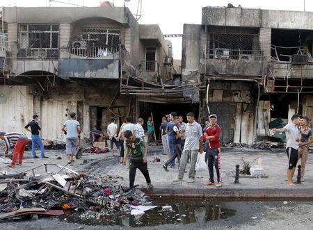 People gather at the site of car bomb in New Baghdad, July 22, 2015. REUTERS/Khalid al-Mousily