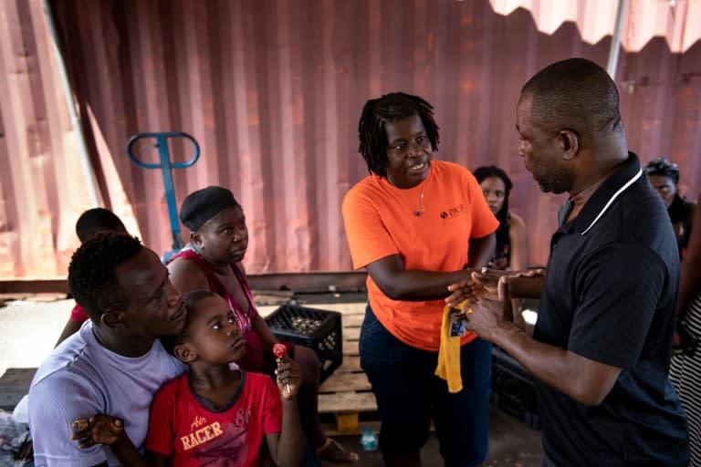 Haiti's charge d'affaires Dorval Darlier (R) talks to survivors of Hurricane Dorian (AFP Photo/Brendan Smialowski)