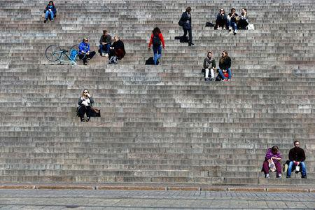 FILE PHOTO: People sit on the steps of Helsinki Cathedral on a sunny day in Helsinki, Finland, May 3, 2017. REUTERS/Ints Kalnins/File Photo