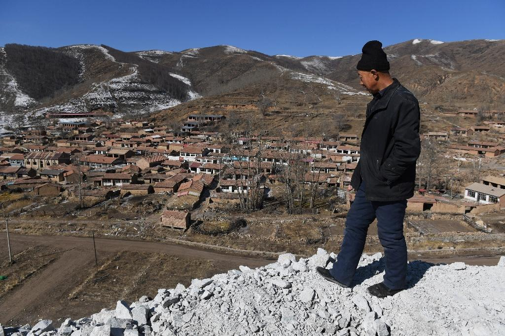 Rsident Ying Gui looks over a village that is to be demolished to make way for the 2002 Winter Games (AFP Photo/Greg Baker)
