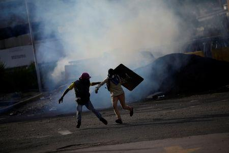 Demonstrators run away at a rally during a strike called to protest against Venezuelan President Nicolas Maduro's government in Caracas, Venezuela July 27, 2017. REUTERS/Ueslei Marcelino