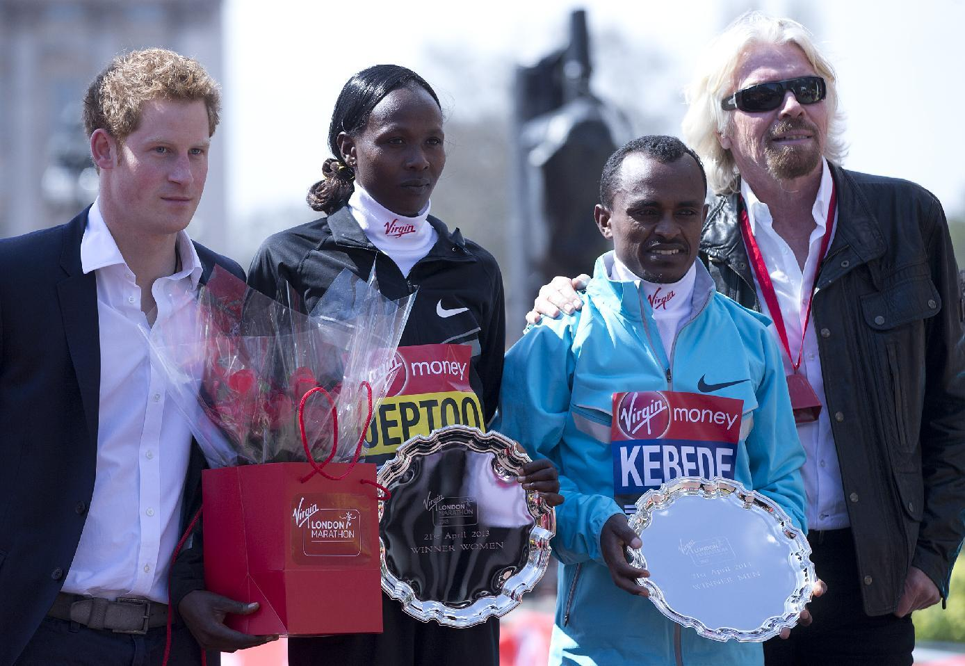 Tsegaye Kebede of Ethiopia, second right, winner of the men's marathon, Priscah Jeptoo of Kenya, second left, winner of the women's marathon with Britain's Prince Harry, left, and British businessman Richard Branson, right, pose together after the medal presentations for the London Marathon in the Mall, Sunday, April 21, 2013. A defiant, festive mood prevailed Sunday as the London Marathon began on a glorious spring day despite concerns raised by the bomb attacks on the Boston Marathon six days ago, as thousands of runners offered tributes to those killed and injured in Boston, with a moment of silence before the race, and many wore black ribbons as a sign of solidarity.(AP Photo/Alastair Grant)