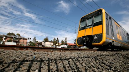 One dead, woman trapped after car collides with train