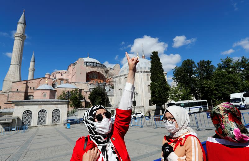 A woman gestures in front of the Hagia Sophia or Ayasofya, after a court decision that paves the way for it to be converted from a museum back into a mosque, in Istanbul