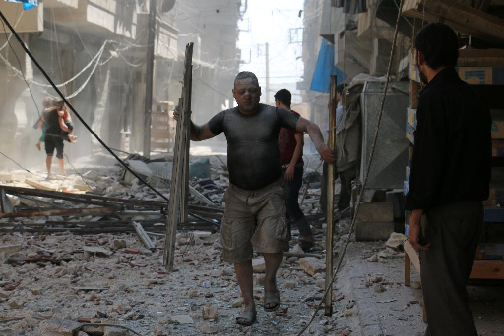 A Syrian man makes his way through the rubble following a reported air strike on a rebel-held neighbourhood of Aleppo, on August 15, 2016