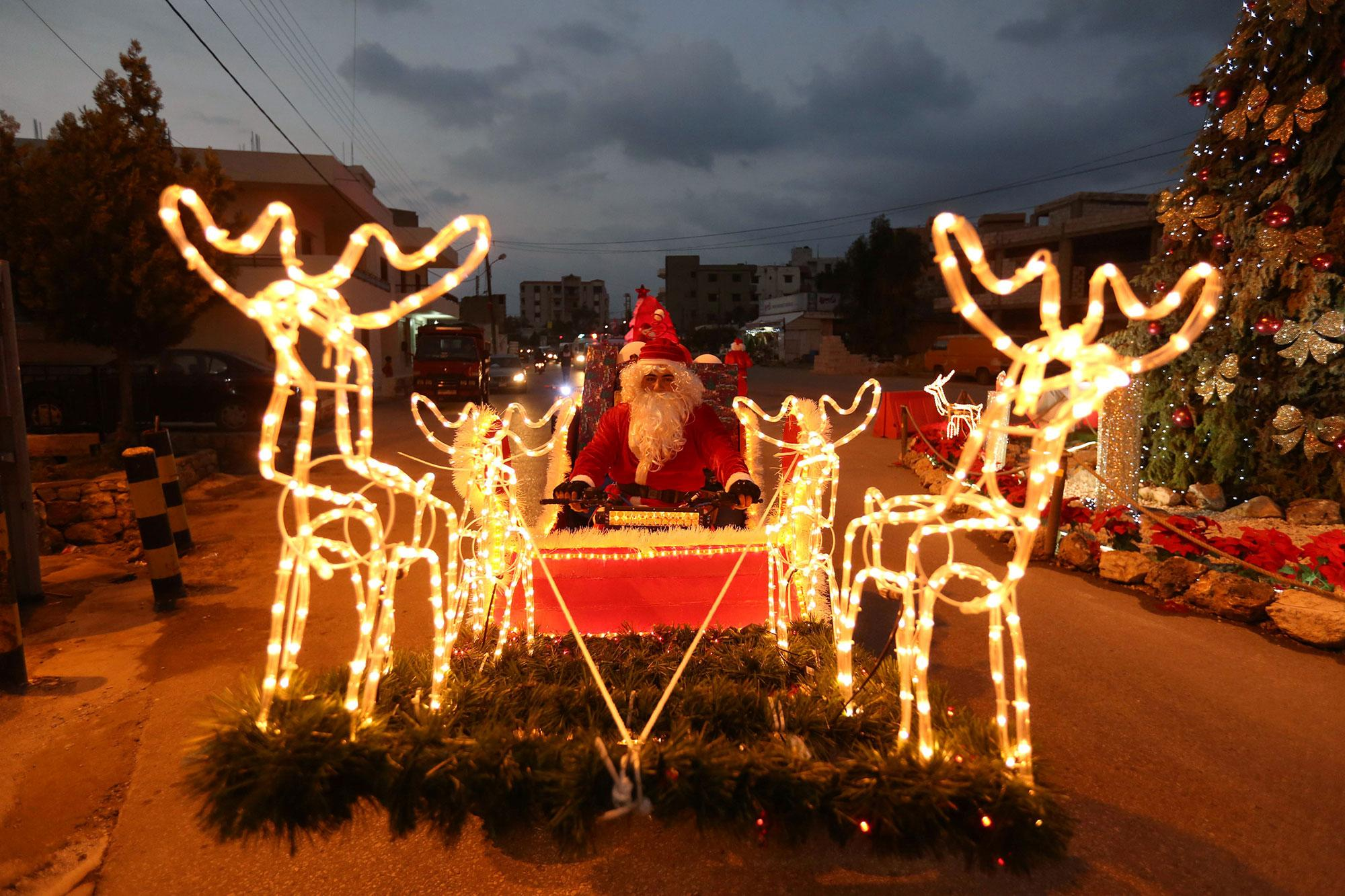 <p>A man dressed as Santa Claus rides a Christmas decorated vehicle in Jiyeh, south Lebanon on Dec. 23, 2016. (Photo: Aziz Taher/Reuters) </p>