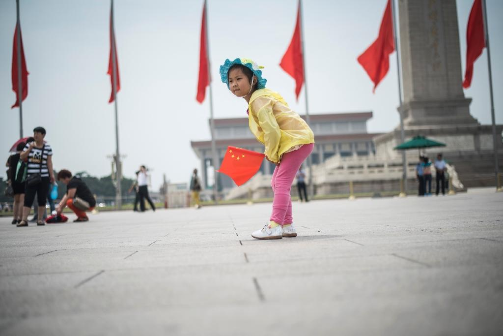 A Chinese girl holds the national flag in Tiananmen Square in Beijing on June 3, 2016, a day ahead of the 27th anniversary of the crackdown on pro-democracy protests (AFP Photo/Fred Dufour)