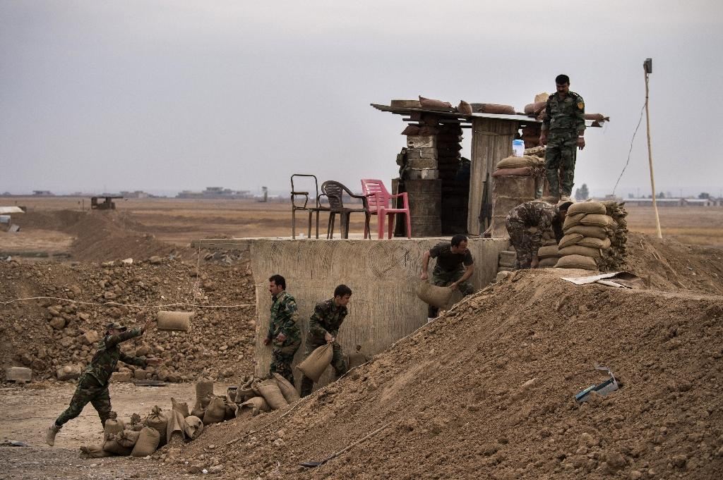 Peshmerga fighters fortify their position along a sand berm north of Shaqouli (AFP Photo/Odd Andersen)