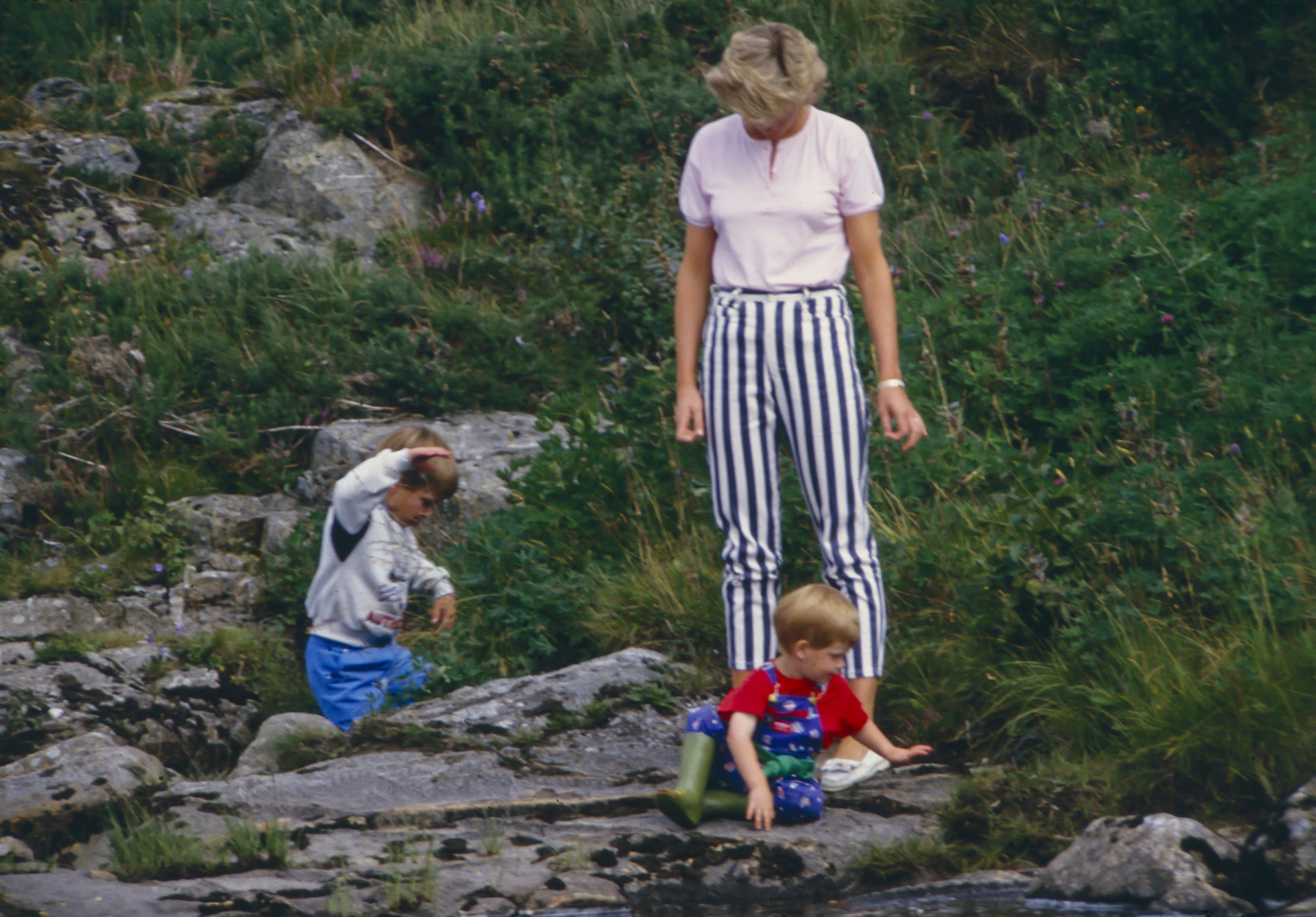 BALMORAL, SCOTLAND  -  AUGUST 18:   Diana, Princess of Wales, Prince William, and Prince Harry play on the banks of the River Dee, near Balmoral Castle.during a Summer vacation, on August 18, 1987, in Balmoral, Scotland. (Photo by Julian Parker/UK Press via Getty Images)