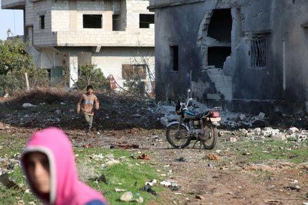 Boys are seen near a damaged house after a strike on rebel-held Tafas town, in Deraa Governorate, Syria