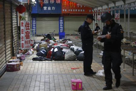 Policemen check unclaimed luggage at a square outside the Kunming railway station after a knife attack, in Kunming