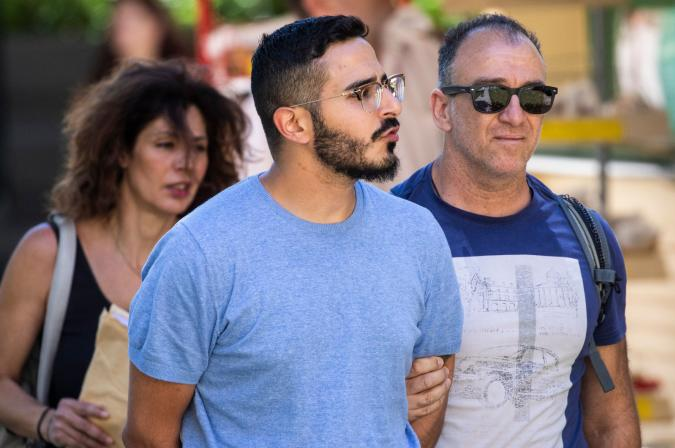 """Picture taken on July 1, 2019 shows the so-called """"Tinder swindler"""" (L) as he is expelled from the city of Athens, Greece. - Police in Greece on Tuesday, July 2, 2019 said they had arrested an Israeli man accused of fraud, named in media reports as the """"Tinder swindler"""" who allegedly defrauded European women he met on the dating site. The suspect has been described in news reports as 28-year-old Simon Hayut. According to Norway's Verdens Gang newspaper, the suspect presented himself as the son of an Israeli multi-millionaire and had defrauded women in Norway, Finland and Sweden out of hundreds of thousands of dollars to fund a lavish lifestyle. (Photo by Tore KRISTIANSEN / various sources / AFP) / Norway OUT        (Photo credit should read TORE KRISTIANSEN/AFP via Getty Images)"""