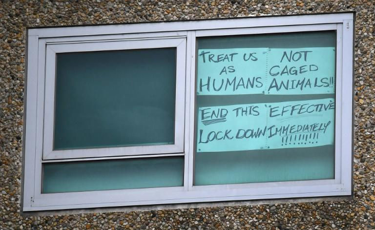 A sign is seen pasted on a window at one of nine public housing estates locked down due to a spike in COVID-19 coronavirus numbers in Melbourne (AFP Photo/William WEST)