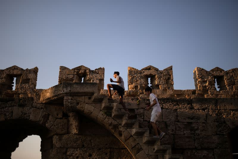 Two boys climb the walls of the castle in the Old Town of Rhodes, following the coronavirus disease (COVID-19) outbreak, on the island of Rhodes