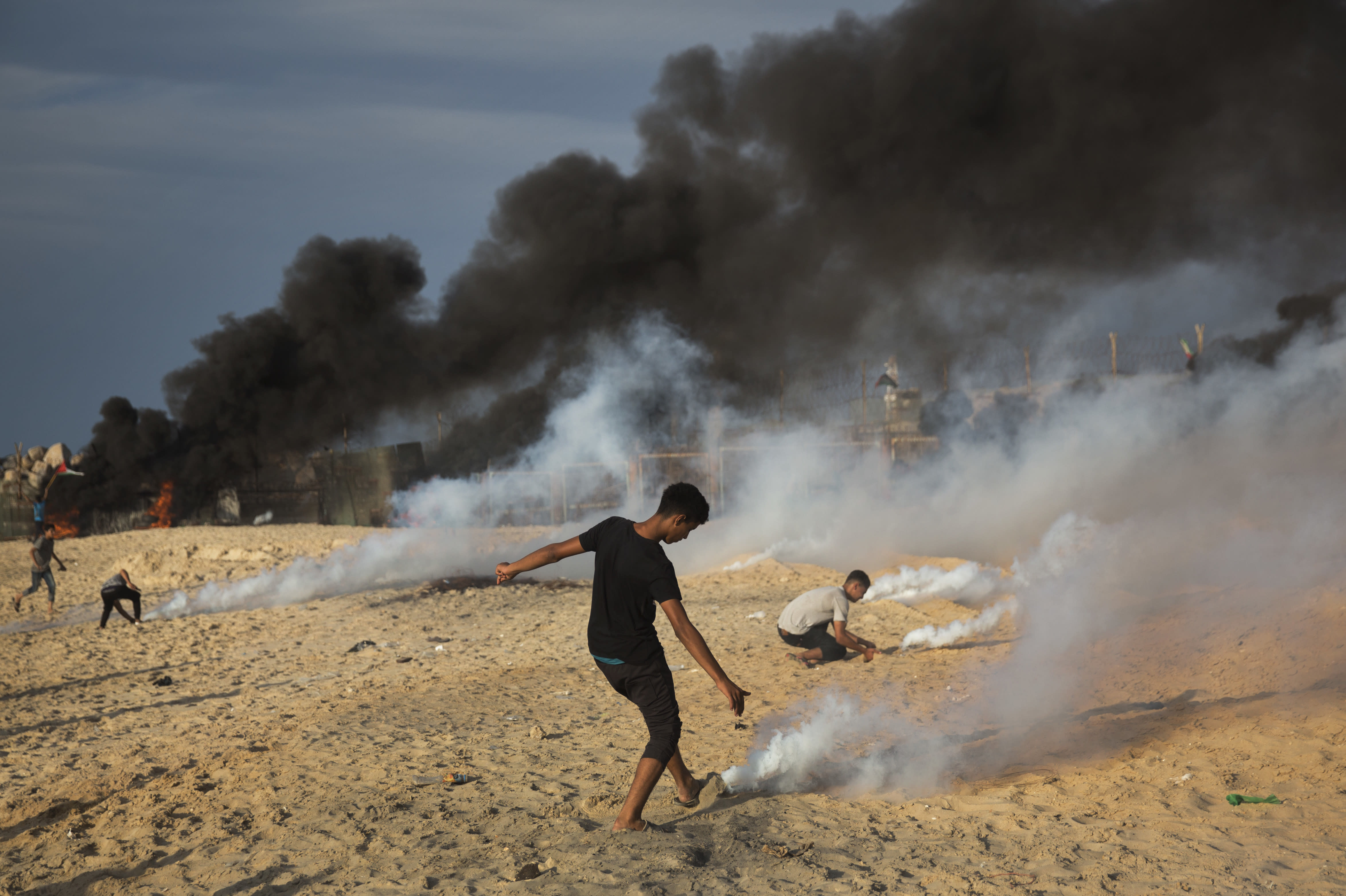 Palestinian protesters cover with sand teargas canisters fired by Israeli troops with sand during a protest on the beach at the border with Israel near Beit Lahiya, northern Gaza Strip, Monday, Oct. 15, 2018.(AP Photo/Khalil Hamra)
