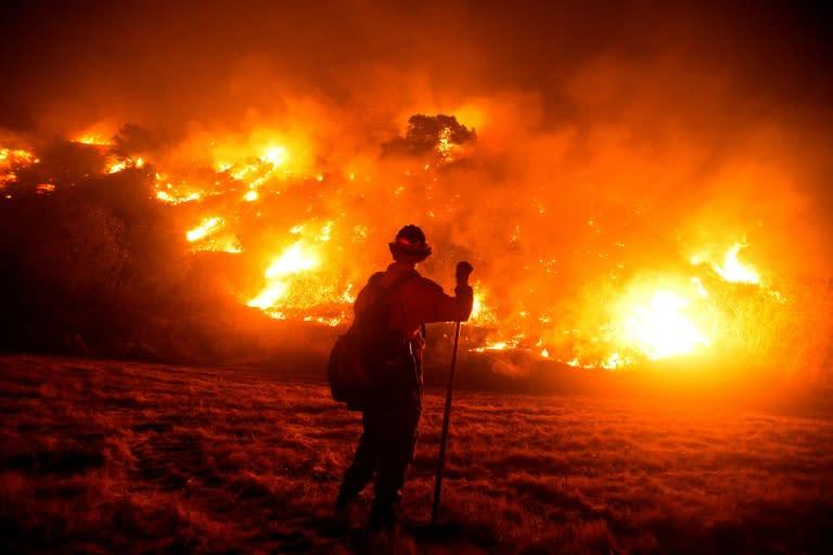 2020年9月15日,一名消防员在山猫大火现场工作,燃烧在加利福尼亚州蒙罗维亚的蒙罗维亚峡谷公园附近的山坡上