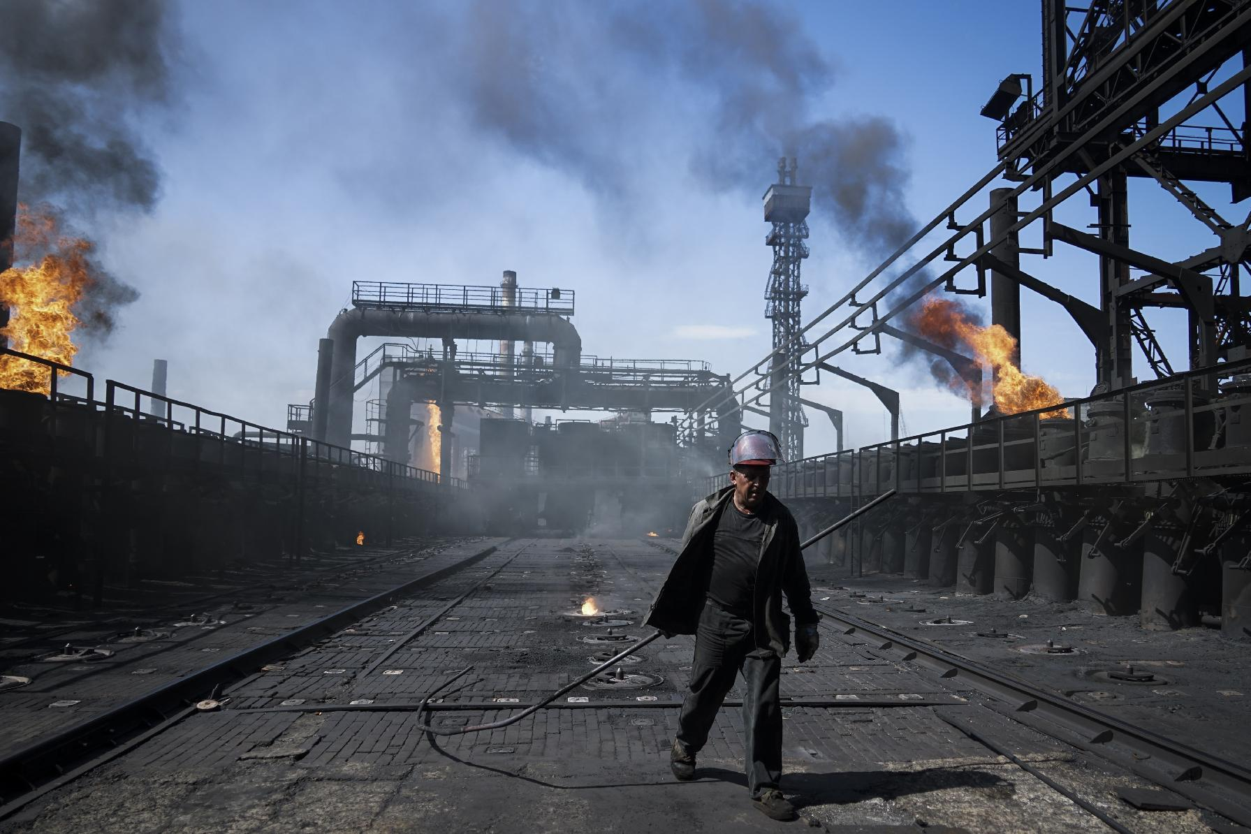 FILE In this Tuesday, Aug. 4, 2015 file photo a worker carries a metal rod at the front-line Avdiivka coking plant in eastern Ukraine. Fighting between government troops and separatist rebels in eastern Ukraine escalated on Tuesday, Jan. 31, 2017, killing several people overnight, injuring many more and trapping 200 coalminers underground, the warring sides reported. (AP Photo/Mstyslav Chernov, File)