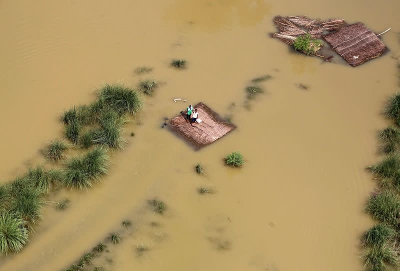 FILE PHOTO: People stand on a partially submerged house as they wait to receive food parcels being distributed by a Indian Air Force helicopter on the outskirts of Allahabad