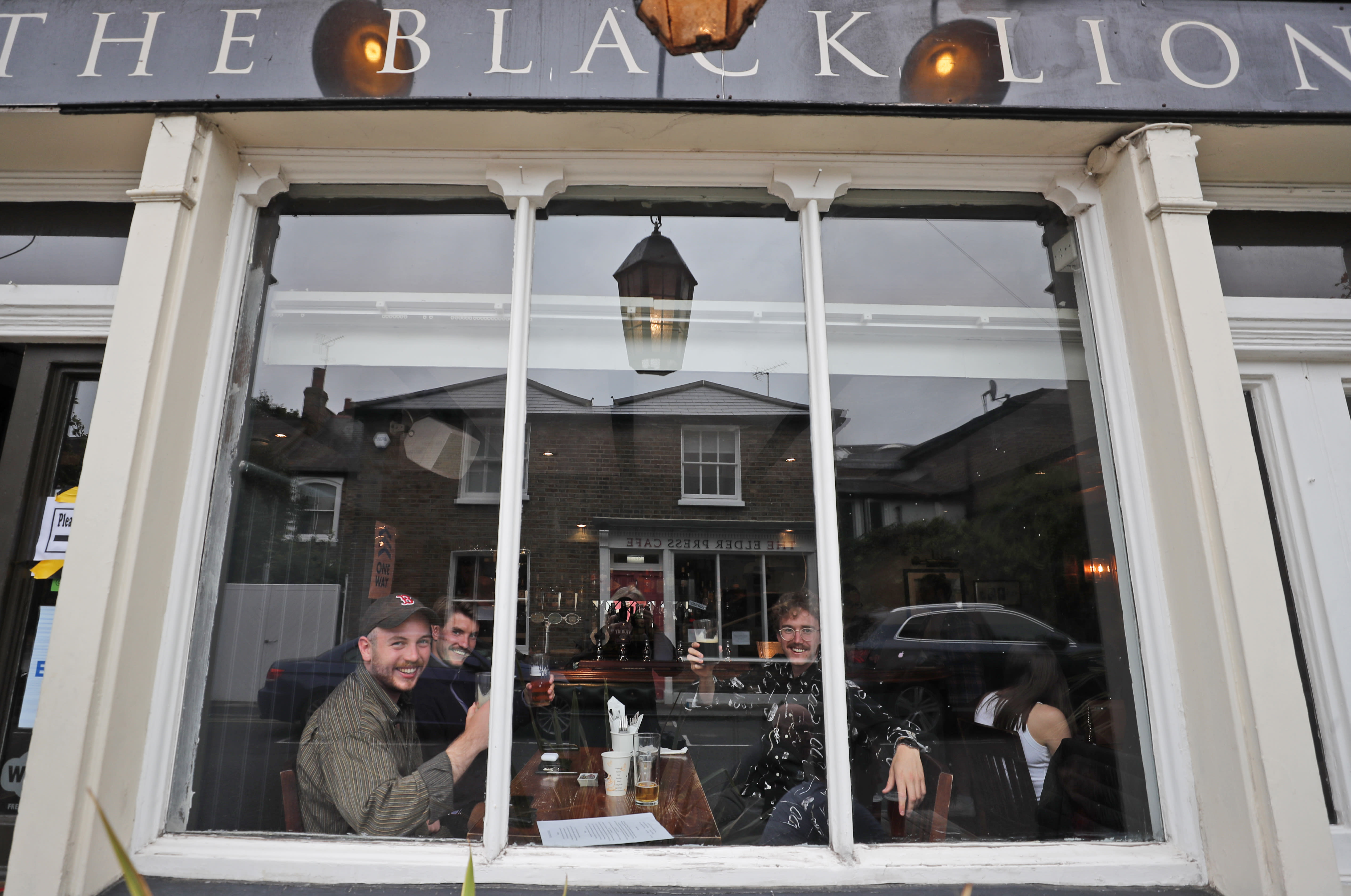 People enjoy their drinks at The Black Lion pub in London, Saturday, July 4, 2020. England is embarking on perhaps its biggest lockdown easing yet as pubs and restaurants have the right to reopen for the first time in more than three months. In addition to the reopening of much of the hospitality sector, couples can tie the knot once again, while many of those who have had enough of their lockdown hair can finally get a trim. (AP Photo/Frank Augstein)