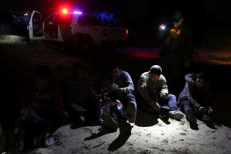 A border patrol agent apprehends immigrants who illegally crossed the border from Mexico into the U.S. in the Rio Grande Valley sector, near McAllen, Texas, U.S., April 2, 2018. REUTERS/Loren Elliott