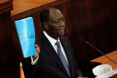 Ivory Coast's President Alassane Ouattara holds the new constitution project document during his speach at the Ivorian parliament in Abidjan October 5, 2016. REUTERS/Luc Gnago